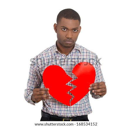 Closeup portrait of young sad confused man, holding broken heart in his hands, about to cry, isolated on white background. Negative human emotion facial expression feelings, attitude - stock photo