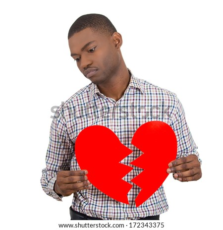 Closeup portrait of young sad confused man, holding broken heart in his hands, about to cry, isolated on white background. Negative emotion facial expression feelings, attitude. Sad Valentine day