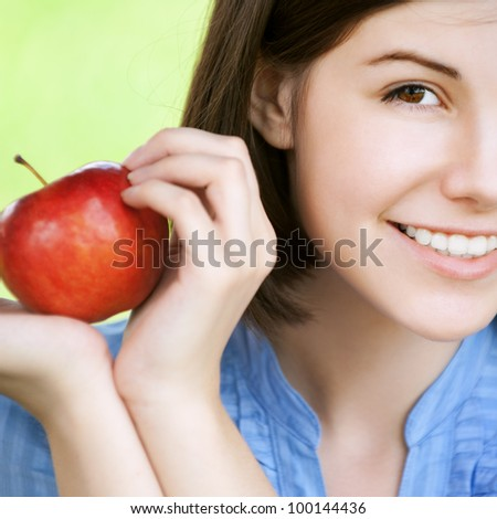 Closeup portrait of young smiling brunette woman holding red apple at summer green park