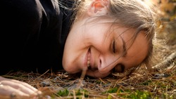 Closeup portrait of young smiling woman lying on ground at forest and listening sound of nature. Concept of ecology, environment protection and harmony with nature.
