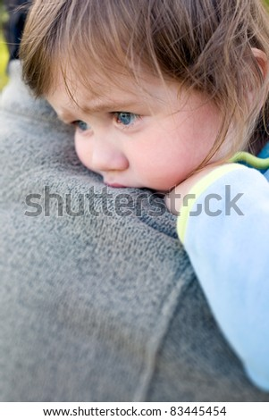 Closeup portrait of young toddler baby girl resting on daddy's shoulder.