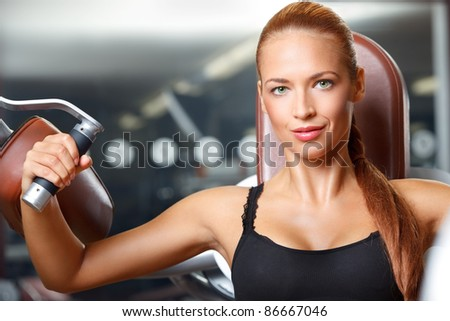 closeup portrait of young woman doing workout on exercise machine in gym