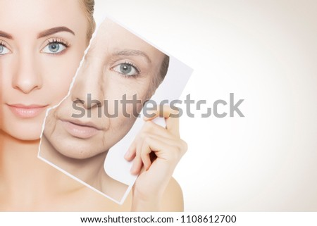 closeup portrait of young woman face holding portrait with old wrinkled face #1108612700