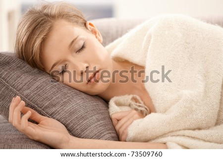 Closeup portrait of young woman sleeping on sofa at home, covered with blanket.