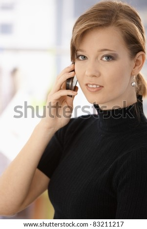 Closeup portrait of young woman, talking on mobile phone. Looking at camera.?
