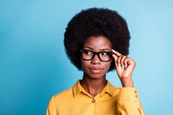 Closeup portrait photo of dark skin big volume hairstyle girl hold eyeglasses serious self-assured curious look empty space wear specs yellow shirt isolated blue color background