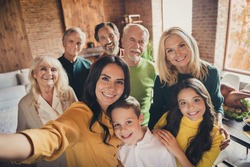 Closeup portrait photo of full big family gathering eight people make selfie cuddle embrace wait pray thank god have good autumn time make wish generation in home evening living room indoors