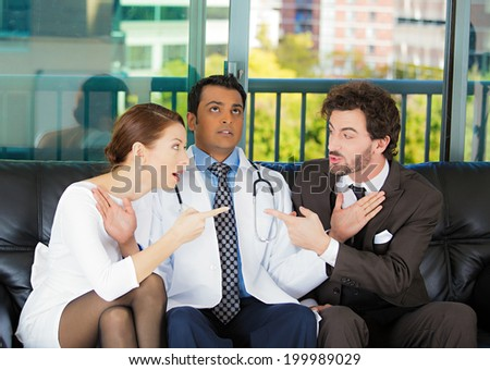 Closeup portrait psychiatrist sitting on black couch caught in between angry couple man, woman trying to push them back in doctor's office isolated city urban background. Negative emotion. Healthcare