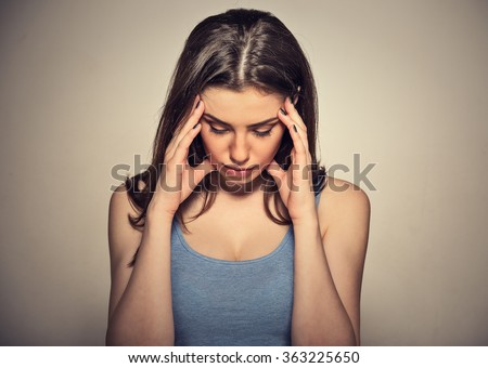 Closeup portrait sad young beautiful woman with worried stressed face expression looking down