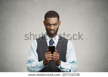 Closeup portrait shocked, displeased, angry, young company businessman unhappy by what he sees on cell phone, isolated black background. Negative human emotion facial expression feeling. Breaking news