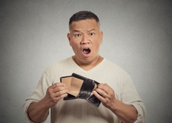 Closeup portrait shocked puzzled unhappy business man worker employee, funny looking guy, student, holding empty wallet isolated grey wall background. Bankruptcy financial difficulty. Face expressions