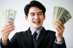 Closeup portrait shot of Asian young handsome black short hair successful rich businessman wears formal suit and necktie laugh and satisfy with full US dollar hundred banknotes currency in hands.