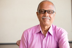 Closeup portrait, smart elderly man in pink shirt with dark eye glasses, specs, sitting down, isolated indoors white chalkboard background