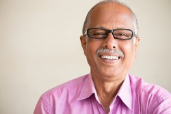Closeup portrait, smart elderly man in pink shirt with dark eye glasses, specs, sitting down laughing, isolated indoors white chalkboard background