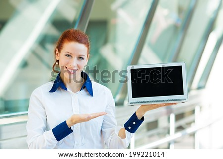 Closeup portrait smiling business woman holding laptop notebook computer, showing something on screen isolated background corporate office windows. Positive facial expression, emotion, attitude #199221014