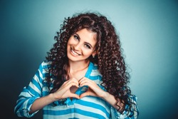 Closeup portrait smiling cheerful happy young curly girl woman making heart sign with hands isolated on blue wall background. Positive human emotion expression feeling life perception body language