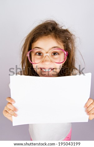 Closeup portrait smiling little, cute, funny looking girl with glasses holding blank piece of white paper isolated grey background. Positive human emotion, facial expression, reaction. Life perception