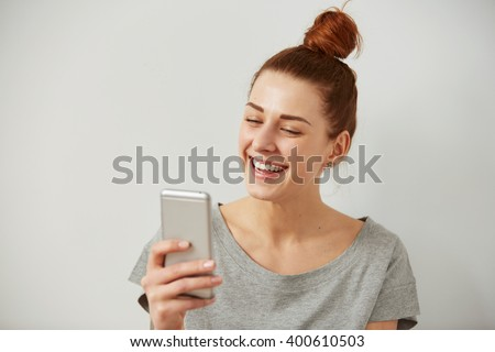 Closeup portrait smiling or laughing young freelancer woman looking at phone seeing good news or photos with nice emotion on her face isolated wall background. Human emotion, reaction, expression.