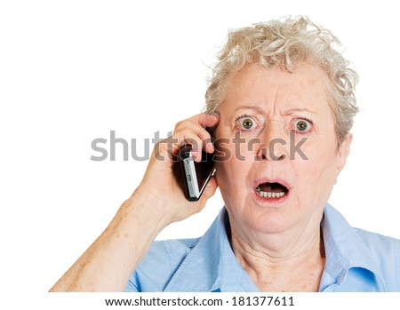 Closeup portrait stressed shocked elderly business woman, senior lady talking on cellular, having unpleasant conversation receiving bad news isolated white background. Human emotion, facial expression