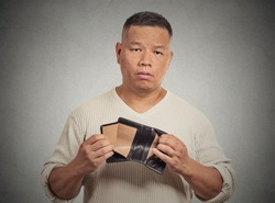 Closeup portrait stressed, upset, sad, unhappy middle aged  man standing with, holding empty wallet isolated grey wall background. Financial difficulties, bad economy concept. Negative emotion