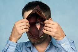 Closeup portrait, stressed, upset, sad, unhappy young man standing with, looking into hole of empty wallet. Financial difficulties, bad economy concept. Negative emotion