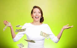 Closeup portrait super excited, laughing young woman who just won lots of money, trying to catch, throw dollar bills in air, isolated green background. Positive emotion, facial expression, feelings