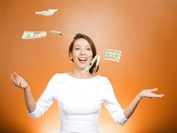 Closeup portrait super excited, laughing young woman who just won lots of money, trying to catch, throw dollar bills in air, isolated orange background. Positive emotion, facial expression, feelings.