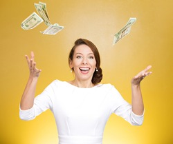 Closeup portrait super excited, laughing young woman who just won lots of money, trying to catch, throw dollar bills in air, isolated yellow background. Positive emotion, facial expression, feelings.