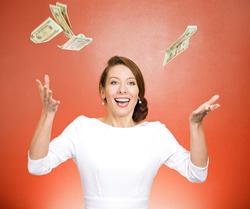 Closeup portrait super excited, laughing young woman who just won lots of money, trying to catch, throw dollar bills in air, isolated red background. Positive emotion, facial expression, feelings