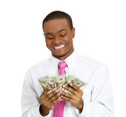 Closeup portrait super happy, excited, successful young man holding money dollar bills in hand isolated white background. Positive emotion, facial expression feeling reaction. Financial reward savings