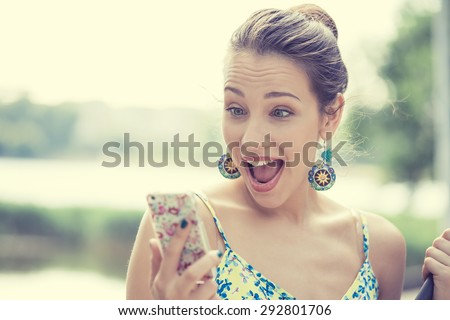 Closeup portrait surprised screaming young girl looking at phone seeing news or photos with funny emotion on her face isolated outside city background. Human emotion, reaction, expression
