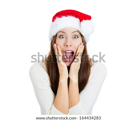 Closeup portrait surprised young beautiful excited happy woman wearing red santa claus hat looking shocked by what she saw isolated white background. Positive emotion facial expression body language