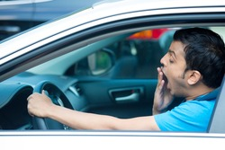Closeup portrait tired young funny man in blue shirt with short attention span, driving his black car after long hours trip, yawning at wheel, isolated outside background. Sleep deprivation
