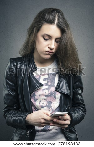 Closeup portrait tired young girl looking at phone seeing bad news or photos with bored emotion on her face texture background. Human emotion, reaction, expression