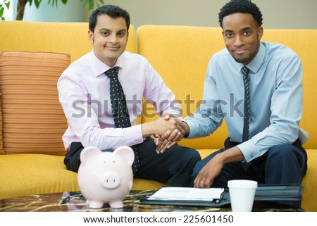 Closeup portrait, two young men in ties shaking hands, isolated yellow couch background with piggy bank and coffee on table foreground #225601450