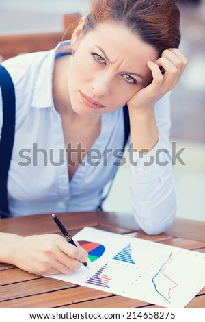 Closeup portrait unhappy business woman looking displeased working on financial report stockholder meeting siting at table documents, writing, distressed, isolated outside. Negative expression emotion