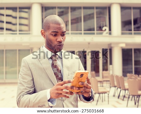 Closeup portrait upset sad skeptical unhappy serious man talking texting on phone displeased with conversation isolated outside city background. Negative human emotion face expression feeling