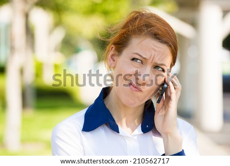 Closeup portrait upset sad, skeptical, unhappy, serious woman talking on phone, displeased with conversation isolated outdoor background. Negative human emotion facial expression feeling. Bad news