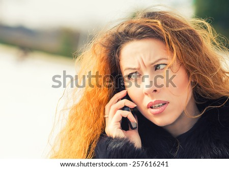 Closeup portrait upset sad, skeptical, unhappy, serious woman talking on phone, standing outdoor. Negative human emotions, facial expressions, feelings, life reaction. Bad news perception