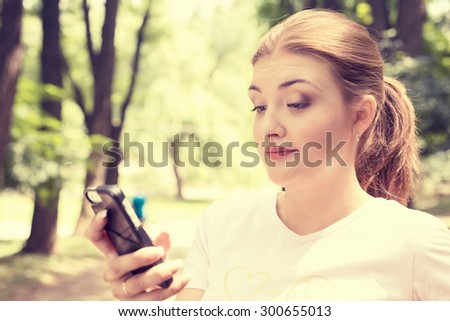 Closeup portrait upset skeptical unhappy serious woman talking texting on phone displeased with conversation isolated park trees outdoors background. Negative human emotion face expression feeling