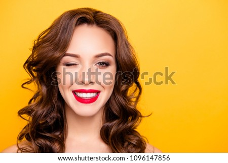 Stock Photo Closeup portrait with copy space empty place of pretty trendy girl with beaming smile red pomade modern hairdo winking with one eye isolated on yellow background