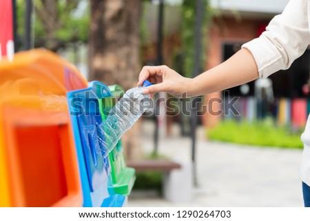 Closeup portrait woman hand throwing empty plastic water bottle in recycling bin. #1290264703