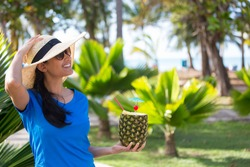 Closeup portrait, woman in blue shirt and brown straw hat holding pineapple mixed drink with rum at resort, isolated background of green palm trees
