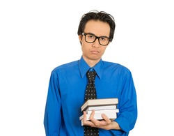 Closeup portrait worried stressed unhappy student with big black glasses standing holding books isolated on white background looking at camera. Human face expression. Education college concept