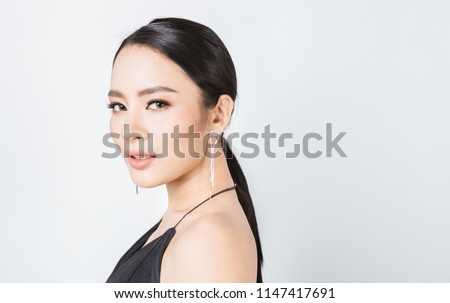 Closeup portrait young beauty asian model fashion girl with diamond earrings black dress. Beautiful face clean fresh perfect skin woman. Facial treatment makeup cosmetic health care makeup spa concept