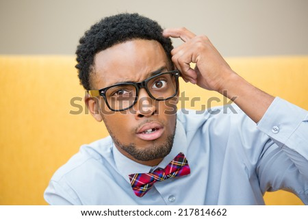 Closeup portrait, young befuddled, bewildered computer geek with big black glasses and bow tie, scratching head wondering about something.