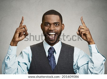 Closeup portrait young business man pointing up  having idea, solution, showing with index finger number one, isolated black grey background. Positive human emotions, facial expressions, symbols, sign