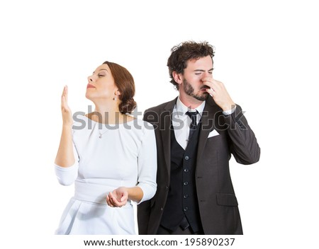 Closeup portrait young couple, man, woman. Female happy smiling, enjoying aroma, male unhappy pinching his nose, disgust face, hates smell isolated white background. Perception contrast, body language