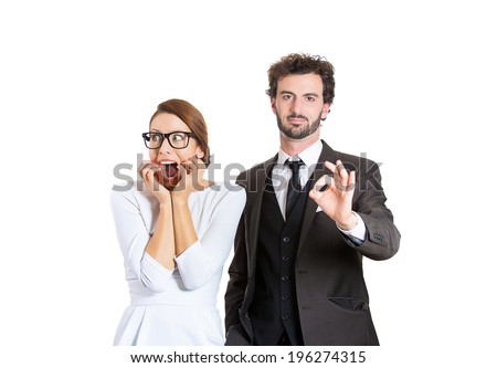 Closeup portrait young couple man, woman. Guy being excited happy, smiling giving ok sign, girl concerned, anxious scared, freaking out biting finger nails, isolated white background. Emotion contrast