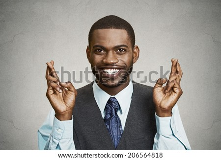 Closeup portrait young funny guy, business man crossing fingers, wishing, hoping for best, miracle isolated black, grey background. Positive human emotions, facial expressions, feelings, attitude
